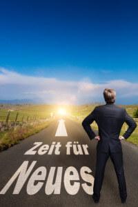 """Geschäftsmann mit Blick auf eine """"open Road"""" beschriftet mit """"Zeit für Neues"""""""