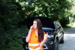 Frau vor SUV telefoniert mit Pannenhelfer