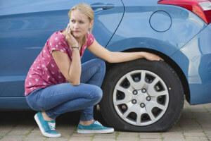 Frau mit Auto und defektem Reifen wartet auf Pannenhilfe